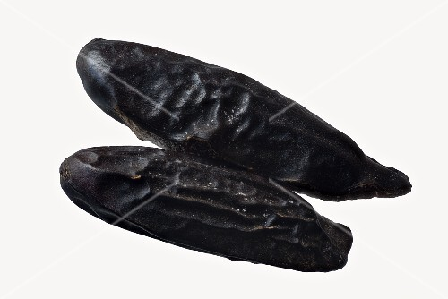 Two tonka beans on a white surface
