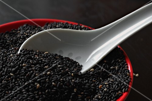 Roasted black sesame seeds with a porcelain spoon in a bowl