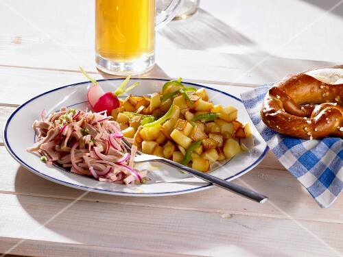 Fried potatoes with a sausage salad, petzels and beer (Bavaria, Germany)