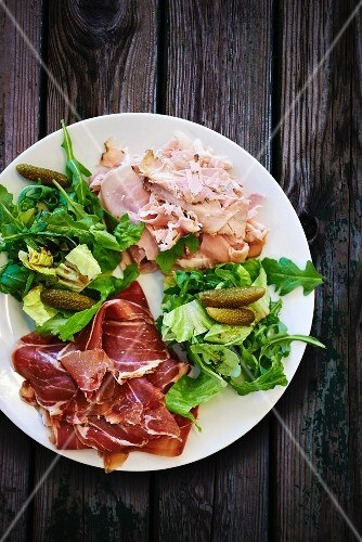 A plate of ham with lettuce and gherkins