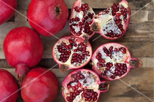 Pomegranates, whole and sliced (seen from above)