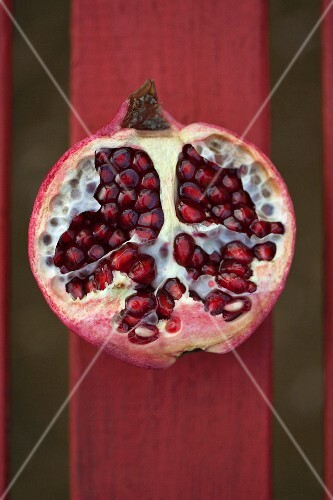 Half a pomegranate on a red wooden slat (seen from above)