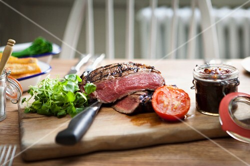 Grilled beef steak with chutney on a wooden chopping board