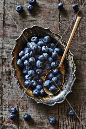 Blueberries in a silver bowl and on a spoon