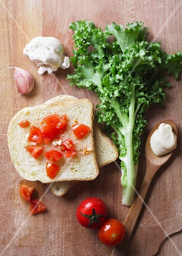 Ingredients for a tomato sandwich with mayonnaise, garlic and lettuce