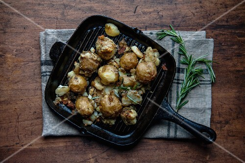 Squashed potatoes in a grill pan with rosemary