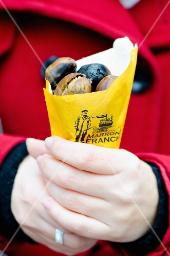 A woman holding a bag of roasted chestnuts
