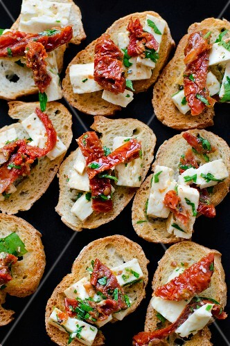 Bruschetta topped with feta cheese, dried tomatoes and herbs (seen from above)