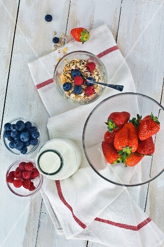A healthy breakfast: muesli with fresh fruits and milk, strawberries, raspberries, blueberries on a wooden table
