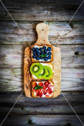 Healthy fruit open sandwiches on a wooden board