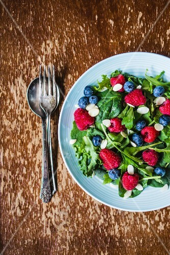 Green salad with rocket, berries and flaked almonds