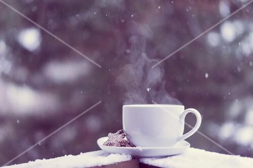 Eine Tasse heißer Tee mit Plätzchen auf Untertasse auf verschneitem Balkon