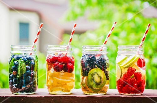 Four fruity drinks in screw-top jars on a garden table