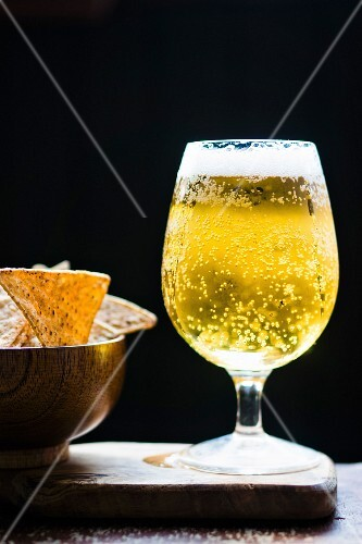 A glass of lager and a bowl of tortilla crisps