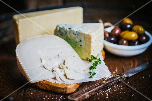 Various types of cheese on a chopping board and a dish of olives