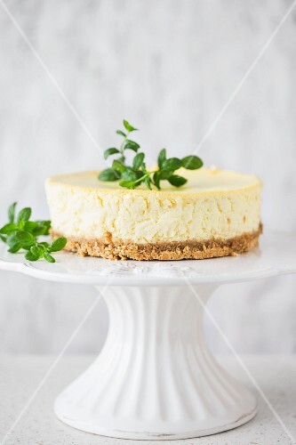 A mojito cheesecake on a cake stand