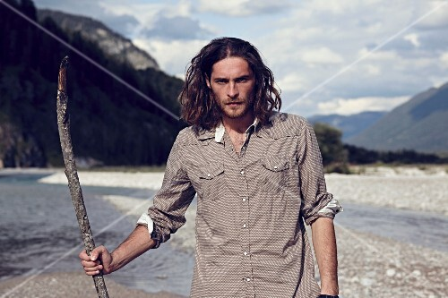 A young man with a beard and long hair walking along a gravelly river bed