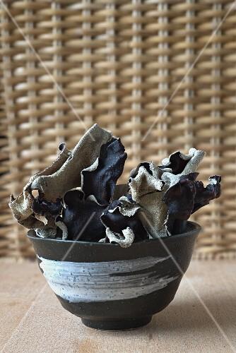 Dried mu-err mushrooms in a ceramic bowl