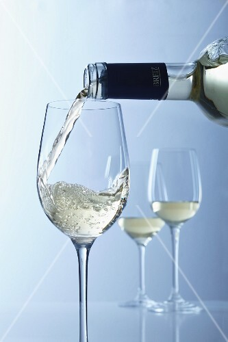 White wine being poured into glasses