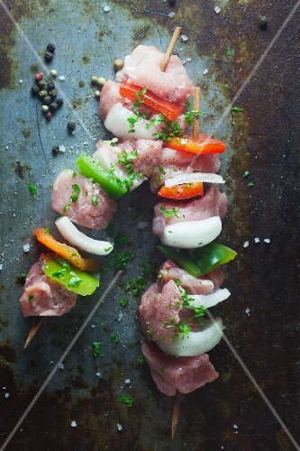 Raw pork skewers with peppers and onions on a metal surface