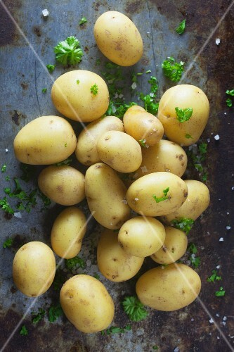 Raw potatoes with salt and parsley on a metal surface
