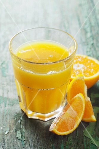 A glass of orange juice on a green wooden surface