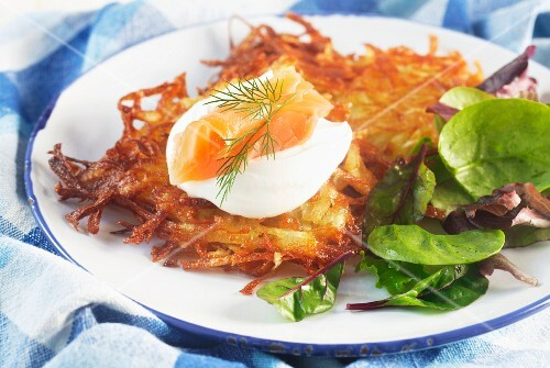 Potato cakes with sour cream and smoked salmon on a blue-and-white plate