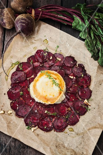 Beetroot carpaccio with goat's cheese on a piece of baking paper