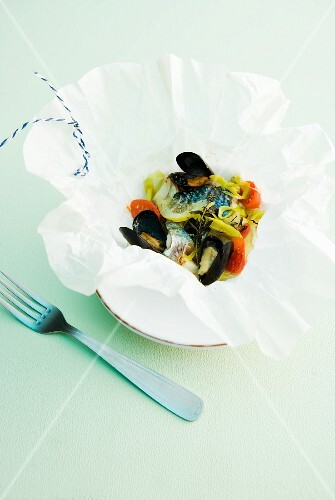 Fish and mussels with leek and tomatoes in parchment paper