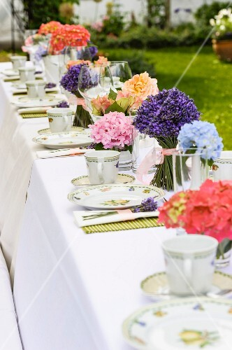 Long table set for afternoon coffee with posies of lavender and other flowers