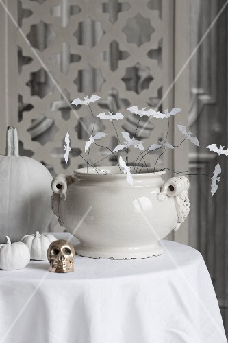 White ceramic bowl decorated with paper bats and small brass skull on white tablecloth on table