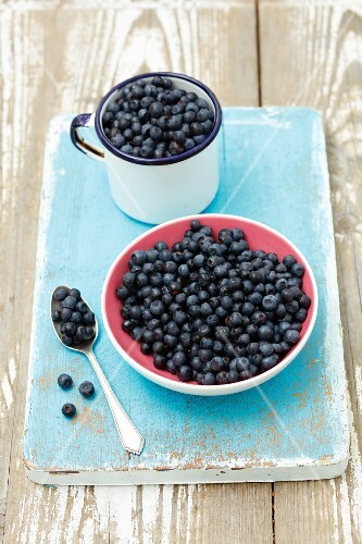 Fresh blueberries in a bowl and in an enamel mug