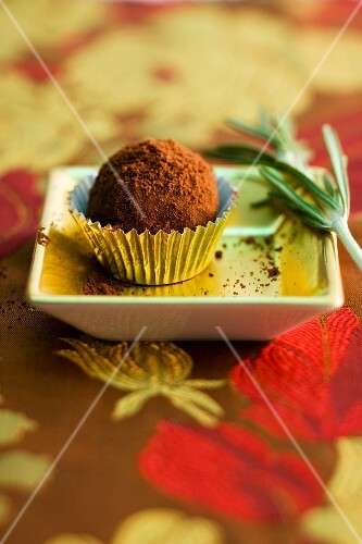 A chocolate truffle with rosemary (close-up)