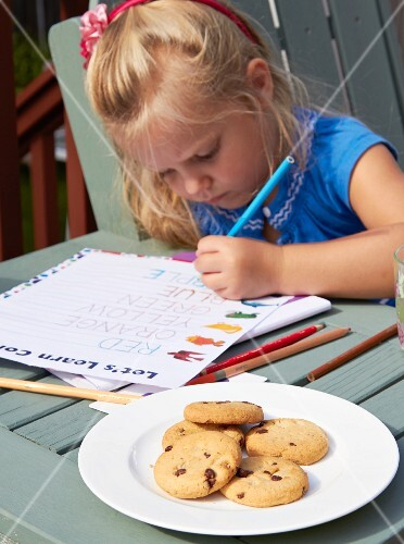 A little girl with a school book and cookies