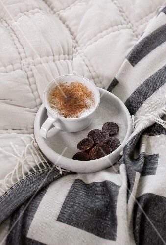Cup of cappuccino and biscuit in marble dish on bed