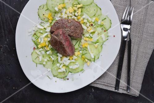 Medium beef tatar on a cucumber and egg salad