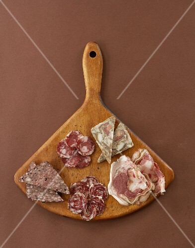 Slices of various Italian meats on a wooden board (seen from above)