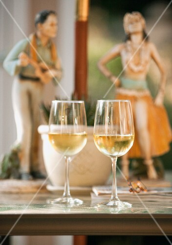 Two glasses of white wine on a table with two Hawaiian statues in the background