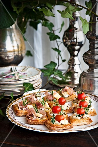 Puff pastry canapés with ham, cheese and tomatoes