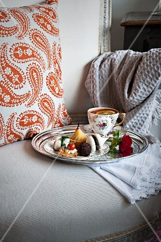 A cup of tea and mini biscuits and spicy canapés on a silver tray on an antique upholstered chair
