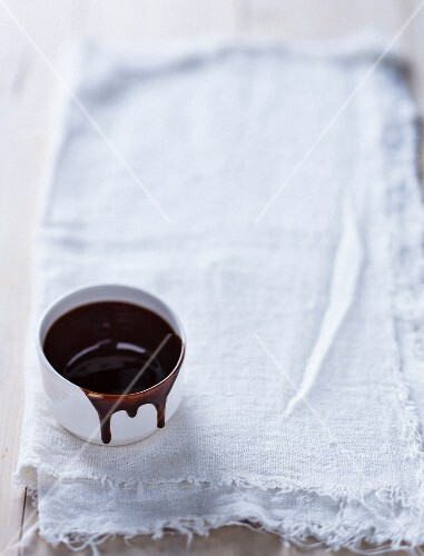 A bowl of chocolate sauce on a linen cloth