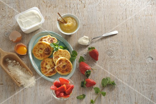 Sirniki (Russian quark pancakes) with apple sauce and strawberries