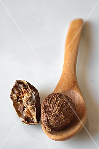 Black cardamom on a wooden spoon and next to it