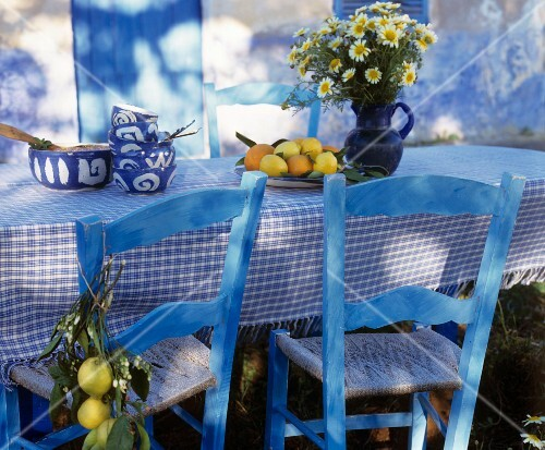 Blue-painted wooden chairs at table with white and blue gingham tablecloth in Mediterranean style