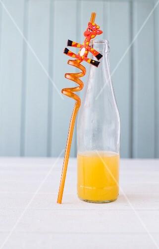 Orangeade in a glass bottle with a giraffe straw