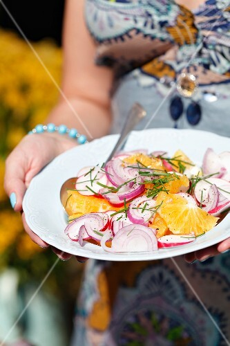 A woman carrying an orange and radish salad