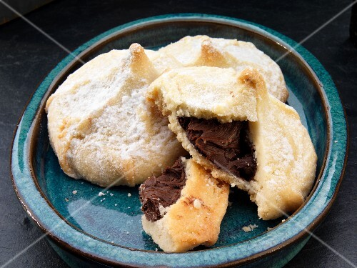 Shortbread cookies filled with chocolate dusted with icing sugar (broken)