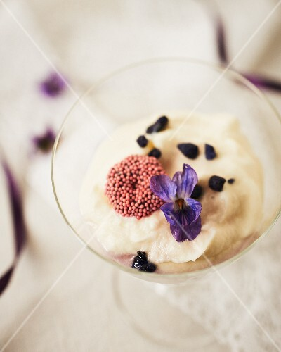 Violet flowers on white chocolate mousse