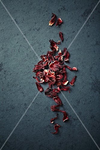 Dried hibiscus flowers on a stone surface