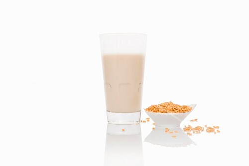 A glass of grain milk on a white surface